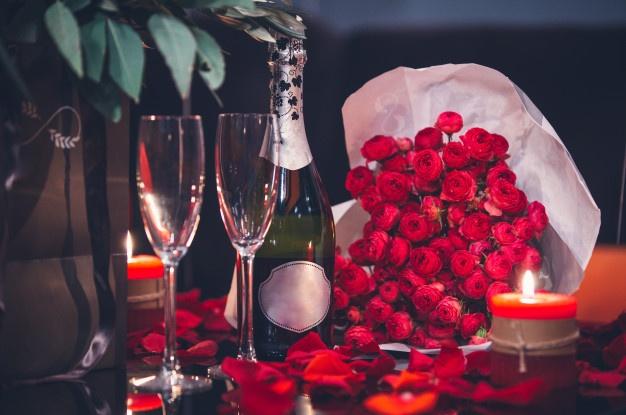 czerwone-roze-dwie-szklanki-butelka-szampana-i-swieca-na-stole_114579-2479