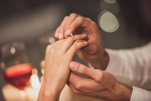 Cropped image of man putting on an engagement ring on his girlfriend's finger while they sitting at the tablet in a restaurant